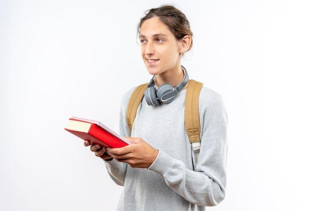 책을 들고 목에 헤드폰으로 배낭을 입고 웃는 찾고 측면 젊은 남자 학생