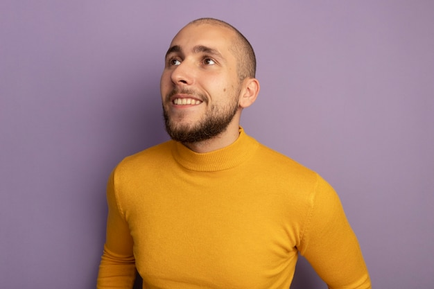 Smiling looking at side young handsome guy isolated on purple wall