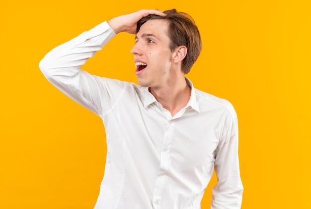 Sorridente guardando lato giovane bel ragazzo che indossa una camicia bianca mettendo la mano sulla testa isolata sul muro arancione
