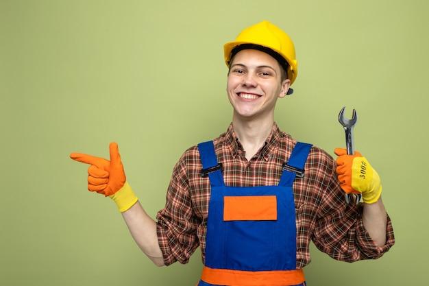 Sorridente cercando lato giovane costruttore maschio che indossa l'uniforme con i guanti che tengono la chiave aperta