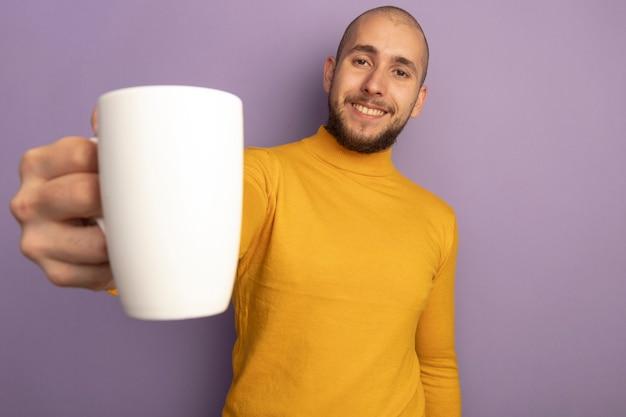보라색에 고립 된 차 한잔 들고 똑바로 젊은 잘 생긴 남자를보고 웃 고