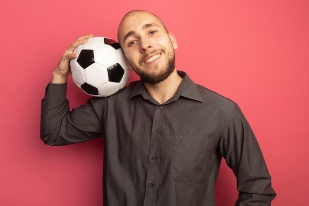 Улыбающийся, смотрящий прямо перед собой молодой красивый парень кладет мяч на плечо изолирован на розовом