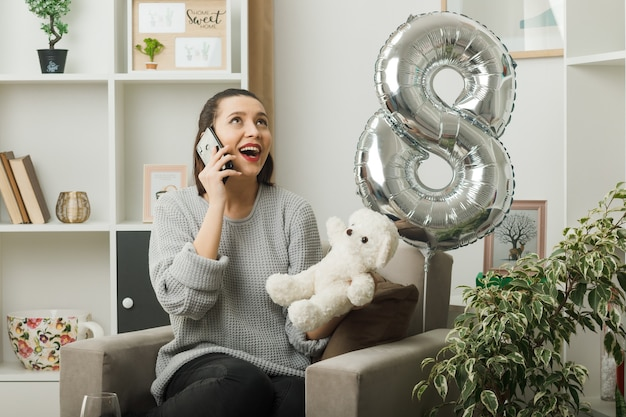 Sorridente guardando la bella ragazza durante la giornata delle donne felici che tiene l'orsacchiotto parla al telefono seduto sulla poltrona in soggiorno