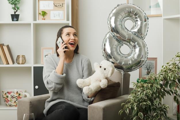 Улыбаясь, глядя вверх красивая девушка в счастливый женский день держит плюшевого мишку, разговаривает по телефону, сидя на кресле в гостиной