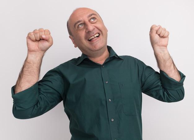 白い壁に分離された握りこぶしを上げる緑のtシャツを着ている中年男性を見上げて笑顔
