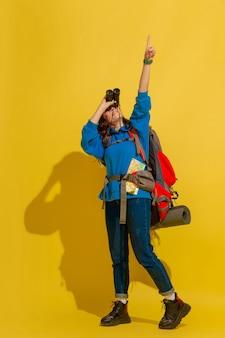 笑顔、見上げる。黄色のスタジオの背景に分離されたバッグと双眼鏡で陽気な若い白人観光客の女の子の肖像画。旅行の準備。リゾート、人間の感情、休暇。