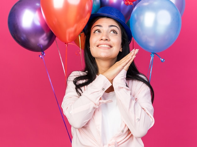 Smiling looking up young beautiful girl wearing party hat standing in front balloons holding hands together isolated on pink wall