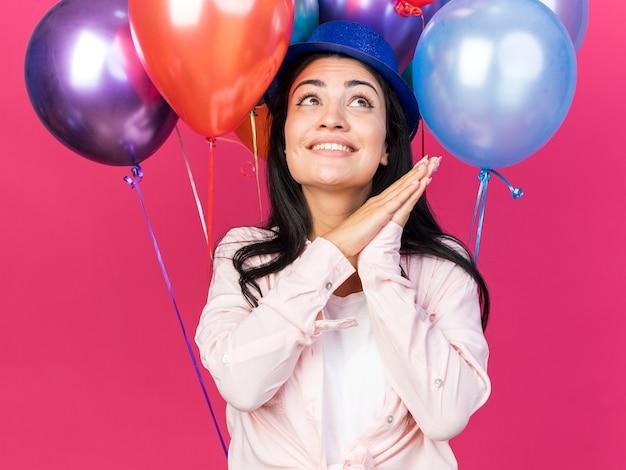 ピンクの壁に分離された手を一緒に持って前の風船に立っているパーティーハットを身に着けている若い美しい少女を見上げて笑顔