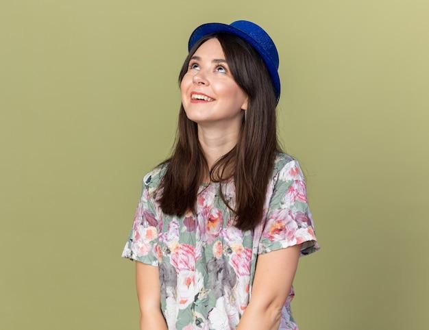 オリーブグリーンの壁に分離されたパーティーハットを身に着けている若い美しい女性を見上げて笑顔