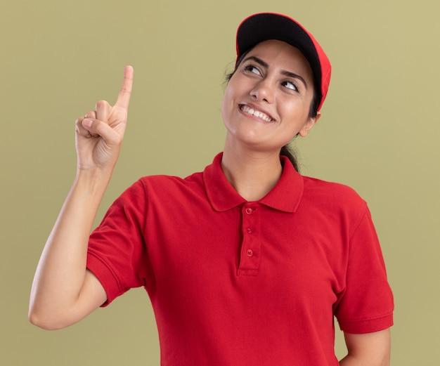 Sorridente guardando la giovane ragazza delle consegne che indossa l'uniforme con il cappuccio punta verso l'alto isolato sul muro verde oliva