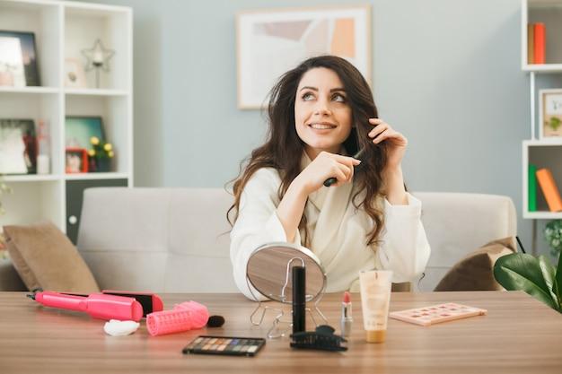 Улыбаясь, глядя вверх, молодая девушка расчесывает волосы, сидя за столом с инструментами для макияжа в гостиной