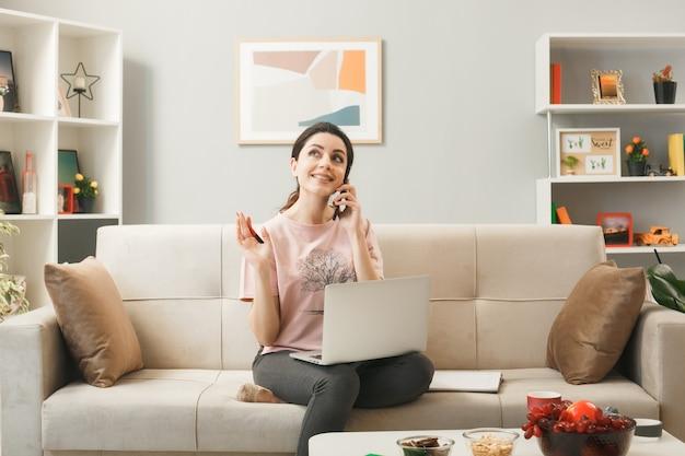 Улыбаясь, глядя вверх, молодая девушка с ноутбуком разговаривает по телефону, сидя на диване за журнальным столиком в гостиной