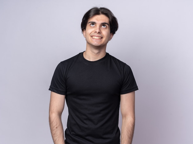 Sorridente guardando il giovane bel ragazzo che indossa una maglietta nera isolata sul muro bianco con copia spazio