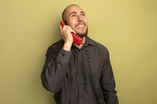 Smiling looking up young handsome guy wearing black t-shirt speaks on telephone