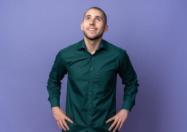 Улыбаясь, глядя вверх молодой красивый парень в зеленой рубашке, кладя руки на бедро