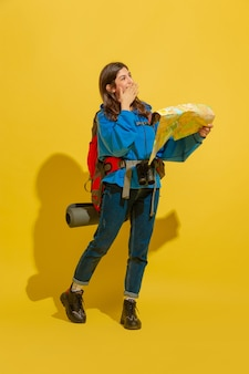 Smiling, looking for way. portrait of a cheerful young caucasian tourist girl with bag and binoculars isolated on yellow studio background.
