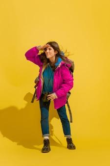 笑顔で、幸せそうに見えます。黄色のスタジオの背景に分離されたバッグと双眼鏡で陽気な若い白人観光の女の子の肖像画。旅行の準備。リゾート、人間の感情、休暇。