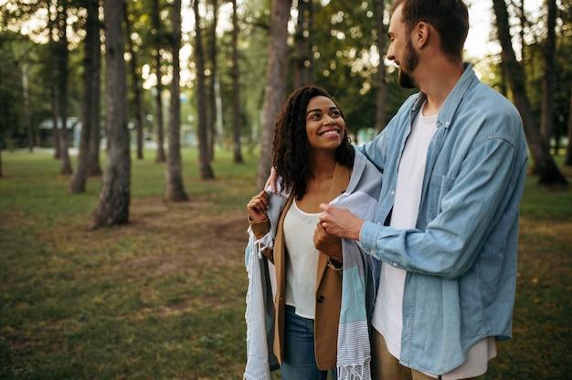 Улыбаясь влюбленная пара обниматься, романтическая прогулка в парке. мужчина и женщина отдыхают на открытом воздухе, зеленая лужайка. семейный отдых на лугу летом, выходные на природе