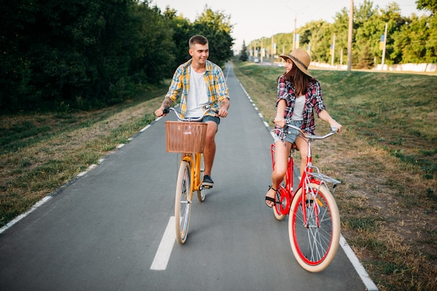 Smiling love couple riding on retro bikes in summer park, romantic date of young man and woman.