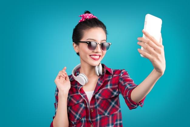 Улыбающаяся симпатичная активная азиатская девушка, делающая селфи фото.