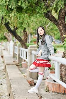 柵に寄りかかって制服を着た素敵なアジアの女の子の笑顔