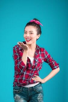 青の上にピンナップスタイルのドレスを着た笑顔の素敵なアジアの女性。