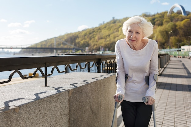 Smiling lovely attractive woman being with crutches thinking about her life while strolling up