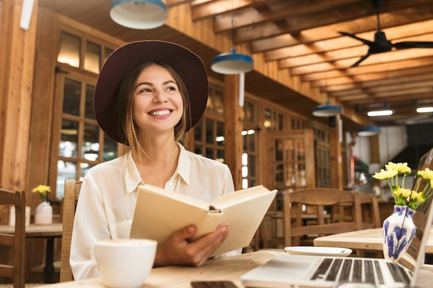 Smiling lovely woman in hat sitting at the cafe table indoors