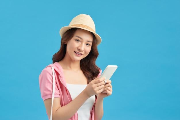 青い背景の上に立って携帯電話を使用して笑顔の素敵な若い女性