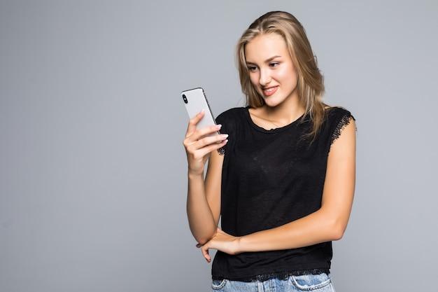 灰色の背景の上に立って携帯電話を使用して笑顔の素敵な若い女性