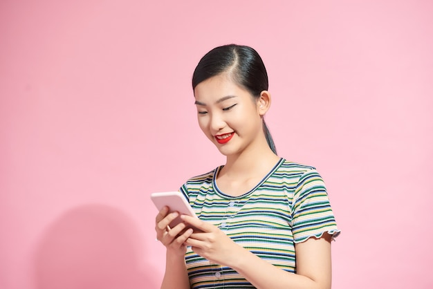 Smiling lovely young woman standing and using cell phone over pink