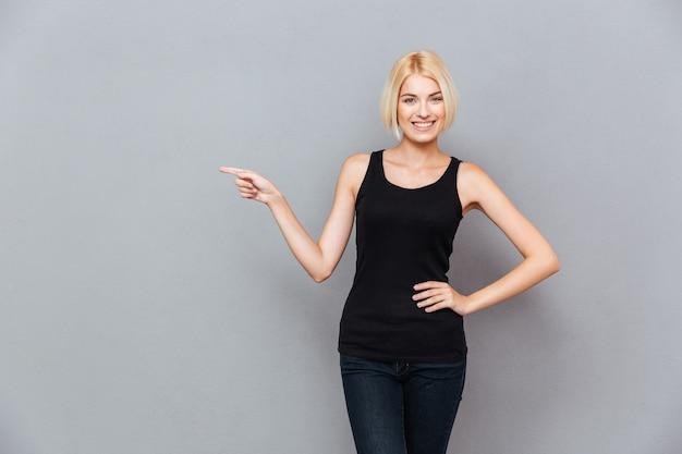 Smiling lovely young womanwith blonde hair pointing away over gray wall