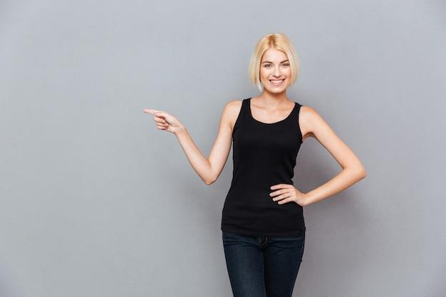 Улыбающаяся милая молодая женщина со светлыми волосами, направленная через серую стену