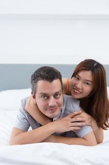 Smiling lovers enjoying honeymoon in hotel