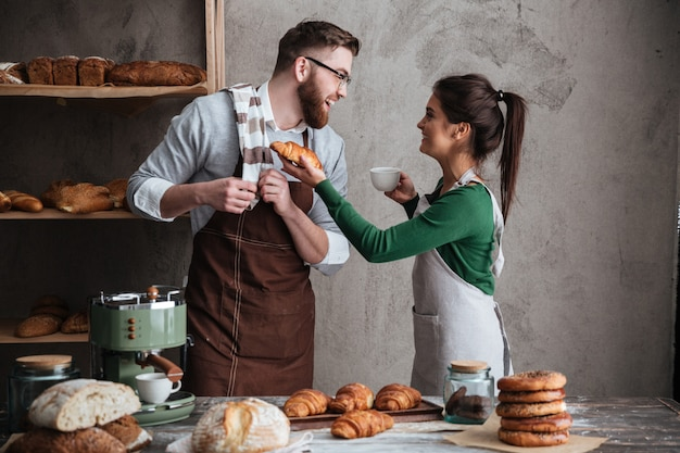 Smiling loving couple bakers drinking coffee.
