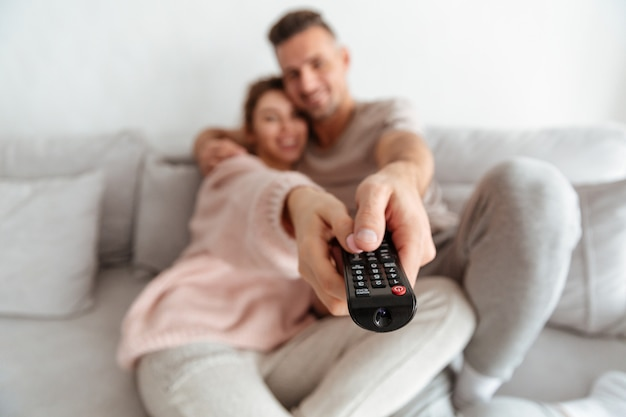 一緒にソファに座ってテレビを見ている愛情のあるカップルの笑みを浮かべてください。テレビのリモコンに焦点を当てる