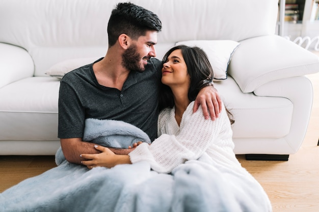 Smiling loving couple sitting in one blanket at living room