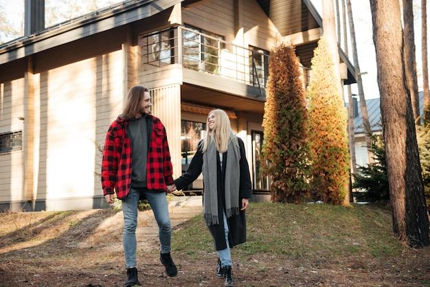 森で野外を歩いている笑顔の愛情のあるカップル。