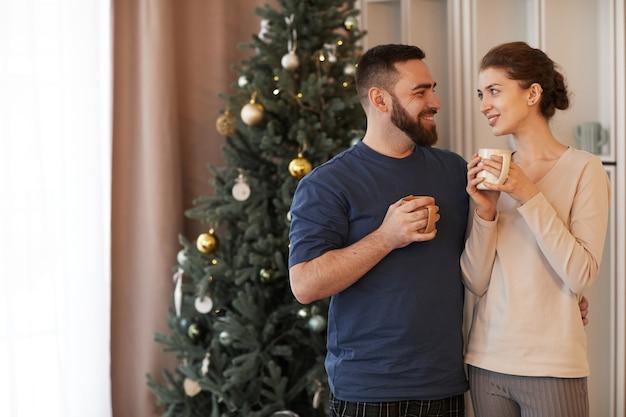 웃고 있는 사랑스러운 젊은 백인 커플이 크리스마스 트리에 기대어 서서 술을 마시는 동안 껴안고 있습니다.