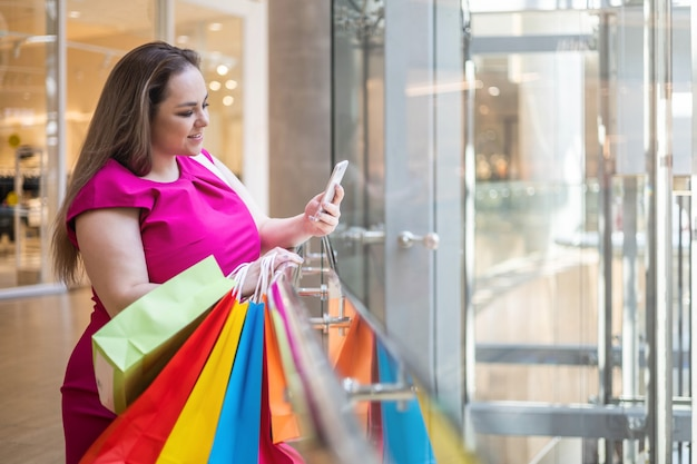 笑顔の贅沢なプラスサイズの金髪の女性が現代のモールで買い物を楽しんでスマートフォンを使用してチャット