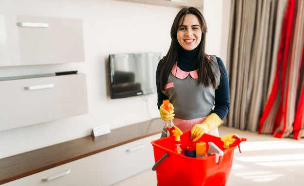 Smiling maid in uniform and rubber gloves standing against cleaning equipment, hotel room interior. professional housekeeping, charwoman