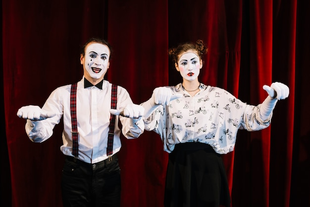 Smiling make mime and sad female mime showing their thumbs on stage