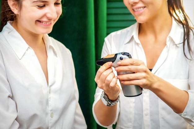 웃는 메이크업 아티스트는 에어 브러시 절차 전에 웃는 클라이언트 에어로 그래프 도구 장치를 보여줍니다.