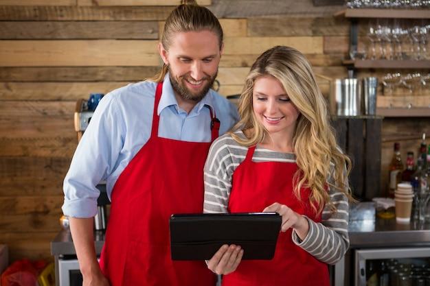 Улыбающиеся бариста мужского и женского пола, использующие цифровой планшет в кафе