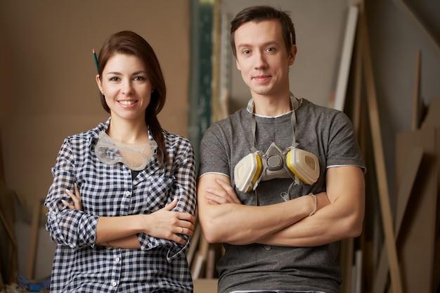Улыбающиеся столяры мужчины и женщины со скрещенными руками, глядя в камеру в мастерской