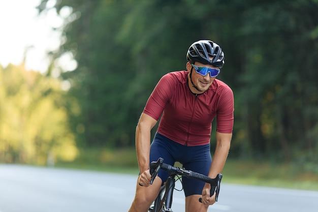 스포츠 의류, 보호 헬멧 및 도로에서 자전거를 타는 미러 안경에 웃는 남자 선수