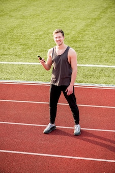 Smiling male athlete standing on race track holding mobile phone in hand