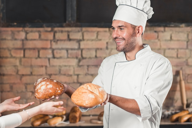 Smiling male baker giving two bread bun to female customer