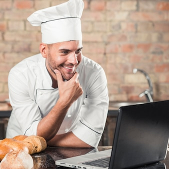 Smiling male baker leaning on kitchen worktop looking at laptop