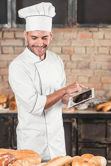 Smiling male baker using digital tablet looking at baked breads on table